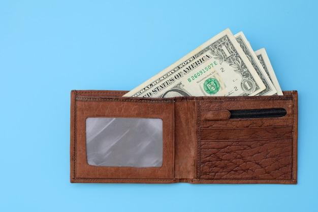 Portafoglio in pelle marrone con banconote in dollari su sfondo blu