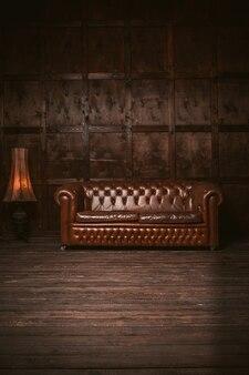 Divano chester in pelle all'interno della stanza in legno con una vecchia lampada da terra. immagine colorata di marrone