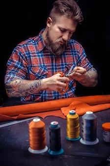 Artigiano della pelle che mostra il processo di taglio della pelle nel suo negozio