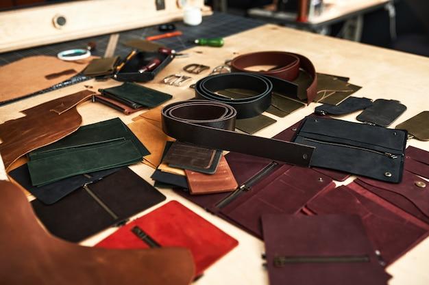 Tavolo da lavoro dell'artigiano in pelle con prodotti, che mostra il flusso di lavoro e il disordine sul posto di lavoro al momento della produzione di prodotti in pelle.