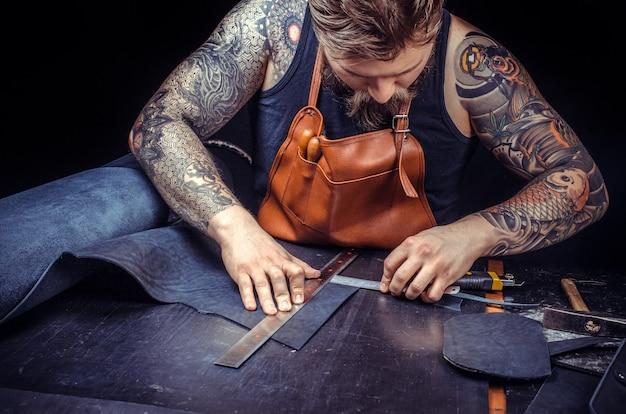 Leather currier ritaglia le forme della pelle per un nuovo prodotto.