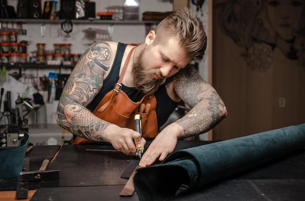 Tagliatore di pelle che produce una lavorazione della pelle sul posto di lavoro.