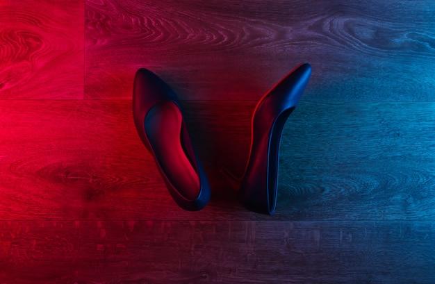 Scarpe tacco alto in pelle sul pavimento in legno con bagliore sfumato rosso-blu al neon