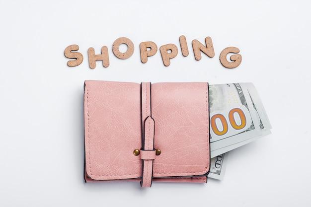 Portafoglio in pelle rosa con banconote e parola shopping