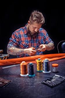 Leather professional crea prodotti di qualità in pelle./leather master al lavoro sul suo nuovo prodotto in pelle nel suo negozio.