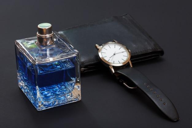 Borsa in pelle, orologio con cinturino in pelle nera e acqua di colonia per uomo su sfondo nero. accessori per uomo. messa a fuoco selettiva sulla bottiglia di profumo.