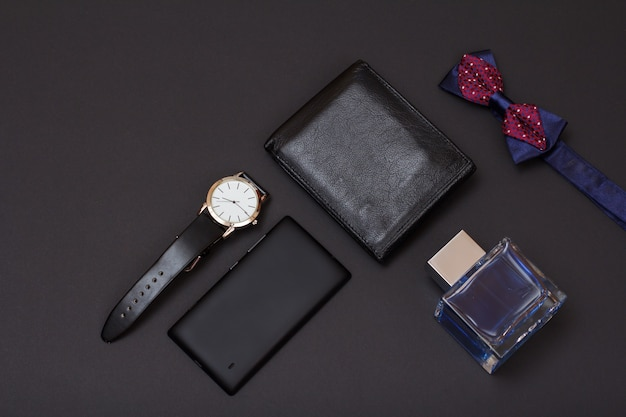 Borsa in pelle, orologio con cinturino in pelle nera, colonia per uomo, papillon e cellulare su sfondo nero. accessori per uomo. vista dall'alto.