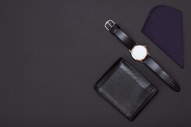 Borsa in pelle, orologio con cinturino in pelle nera e fazzoletto su sfondo nero. accessori per uomo. vista dall'alto con copia spazio.