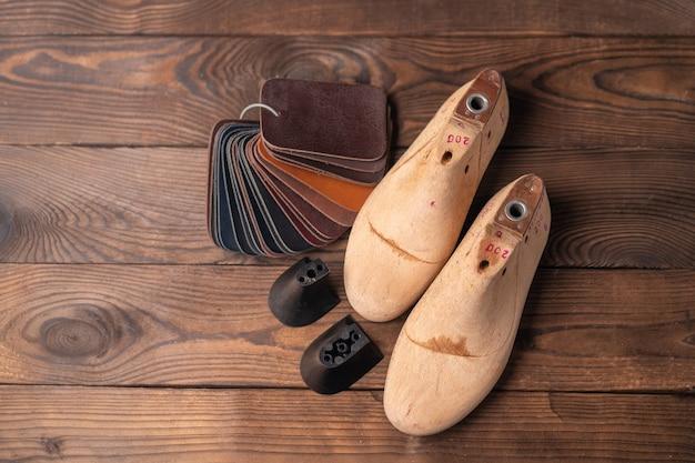 Campioni di pelle per scarpe e forma di scarpa in legno sul tavolo di legno blu. vestiti di mobili di design. area di lavoro del calzolaio.