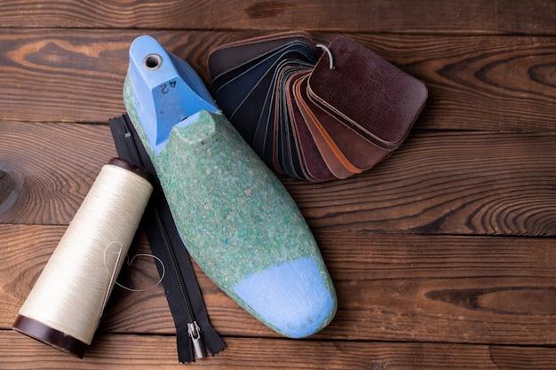 Campioni di pelle per scarpe e forma di scarpa in legno sul tavolo di legno scuro vestiti di mobili di design. area di lavoro del calzolaio.