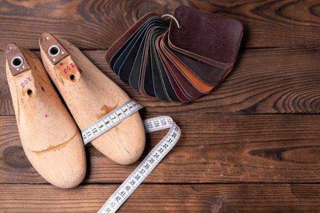 Campioni di pelle per scarpe e forma di scarpa in legno sul tavolo di legno scuro. vestiti di mobili di design. area di lavoro del calzolaio.