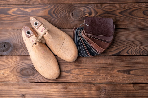 Campioni di pelle per scarpe e forma di scarpa in legno su un tavolo di legno scuro