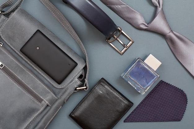 Borsa a tracolla in pelle per uomo con telefono cellulare, cintura per uomo, borsa nera, colonia per uomo, fazzoletto e cravatta su sfondo grigio. accessori per uomo. vista dall'alto