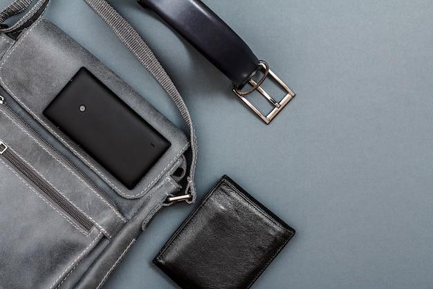Borsa a tracolla in pelle per uomo con telefono cellulare, cintura per uomo e borsa nera su sfondo grigio. accessori per uomo. vista dall'alto con copia spazio