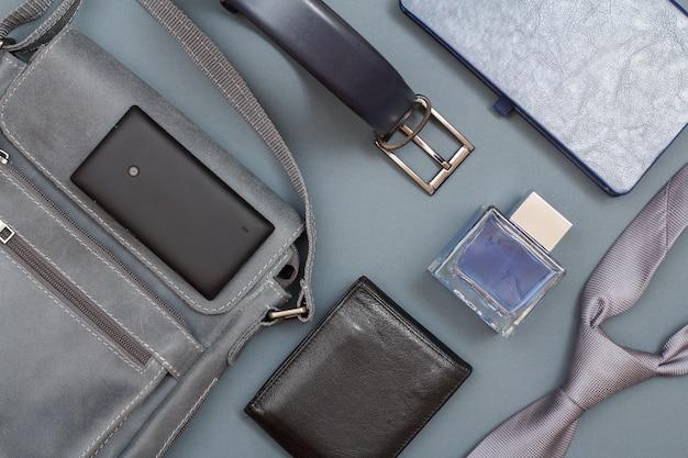 Borsa a tracolla in pelle con telefono cellulare, cintura da uomo, taccuino, borsa, acqua di colonia e cravatta.
