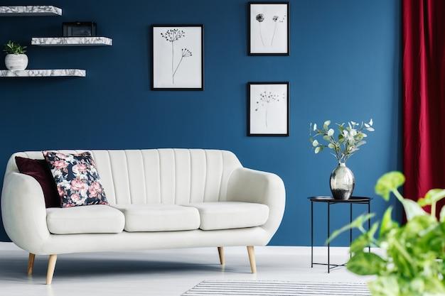 Divano in pelle, dipinti floreali sulla parete blu e fiori in un vaso in un interno del soggiorno