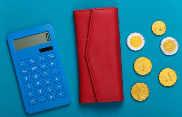 Portafoglio in pelle con monete e calcolatrice su un blu