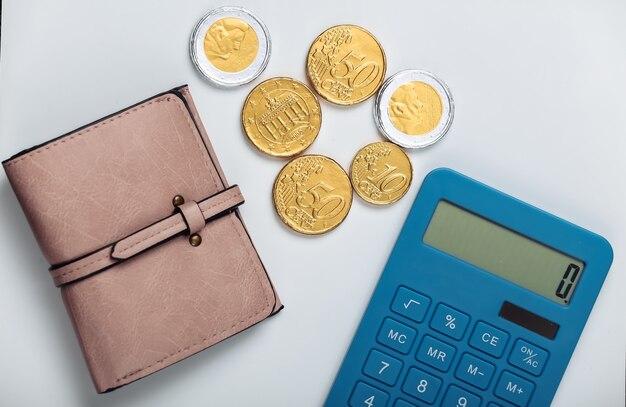 Portafoglio in pelle con monete e calcolatrice su bianco