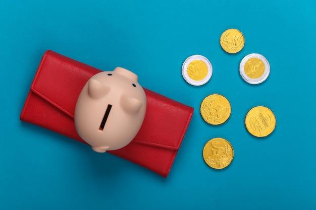 Portafoglio in pelle con monete e salvadanaio su un blu