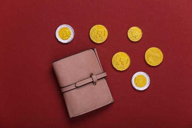 Portafoglio in pelle con monete su rosso