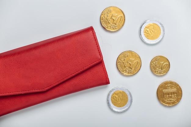 Portafoglio in pelle con monete su bianco