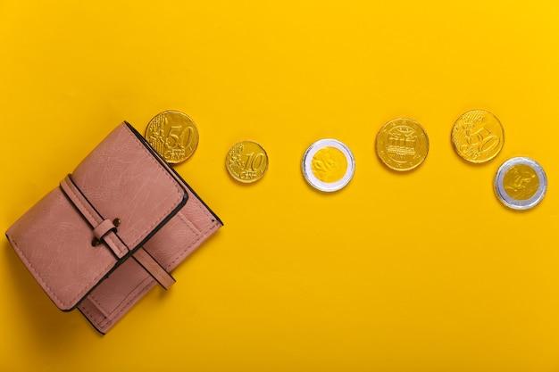 Portafoglio in pelle con monete su giallo