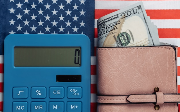 Portafoglio in pelle con banconote da cento dollari, calcolatrice sulla bandiera degli stati uniti.