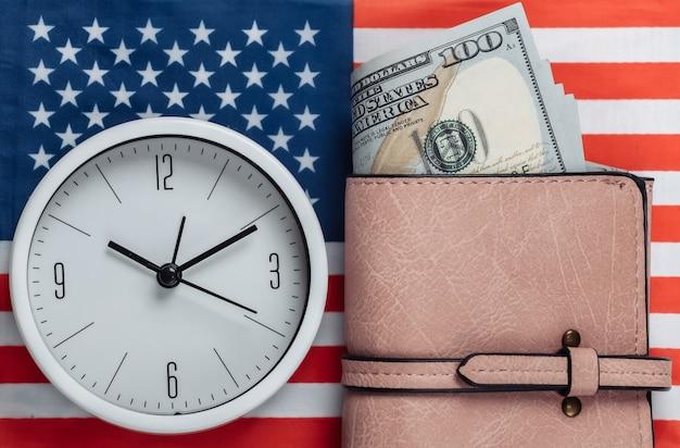 Portafoglio in pelle con banconote da cento dollari, orologio della bandiera degli stati uniti. il tempo è denaro