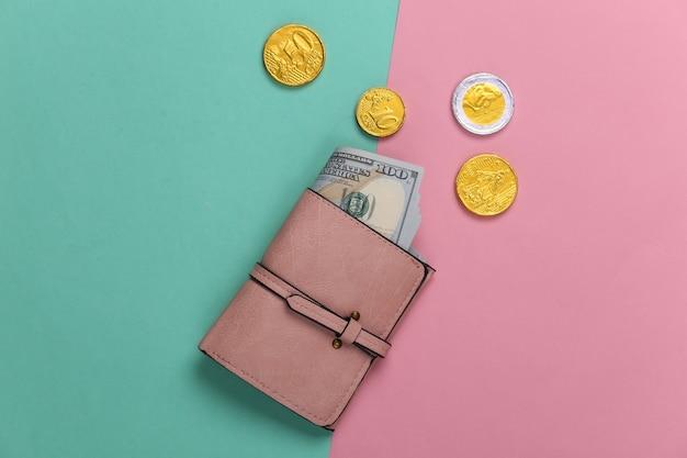 Portafoglio in pelle con banconote da cento dollari e monete su un pastello blu-rosa