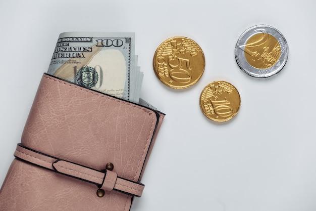 Portafoglio in pelle con banconote da cento dollari e monete su bianco
