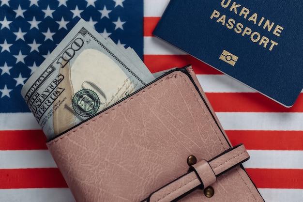 Portafoglio in pelle con banconote da cento dollari, passaporto sulla bandiera degli stati uniti. tema del viaggio o dell'emigrazione