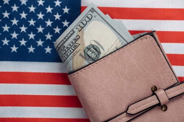 Portafoglio in pelle con banconote da cento dollari sulla bandiera degli stati uniti