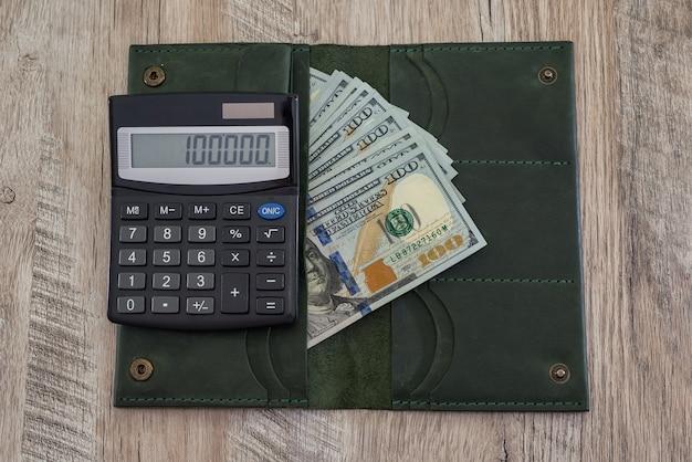 Portafoglio in pelle con dollari usa e una calcolatrice su un tavolo di legno.