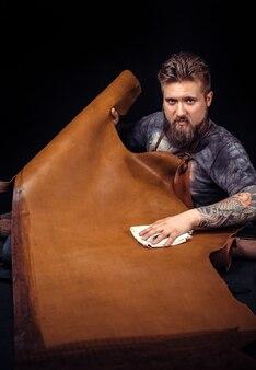 Leather worker che ritaglia le forme di cuoio per un nuovo prodotto