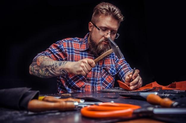 Leather worker lavorando su un nuovo prodotto in pelle presso lo studio di pelletteria