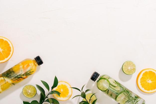 Foglie e bottiglia di acqua tropicale su sfondo bianco. acqua detox alla frutta, agrumi e foglie di rosmarino. vista dall'alto, distesi, copia spazio