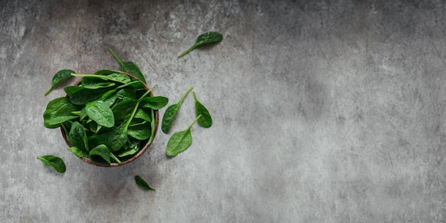 Foglie di spinaci freschi in una ciotola. foglie verdi organiche scure. concetto di stile di vita alimentare vegano sano