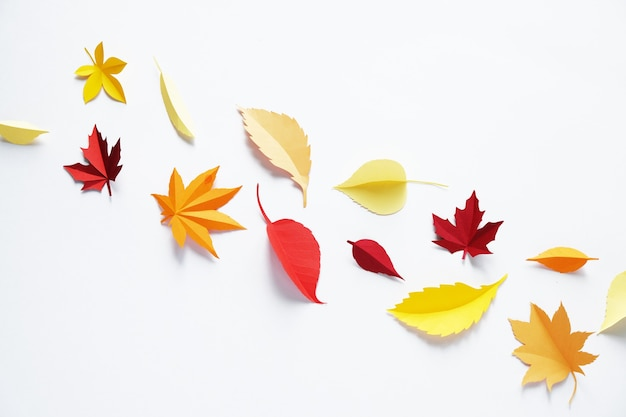 Foglie di carta cadono foglie rosse, arancioni, gialle.