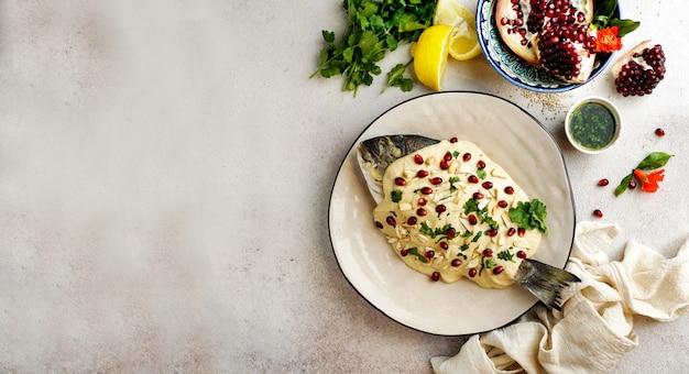 Pesce libanese con salsa tahini, semi di melograno e mandorle (samke harra)