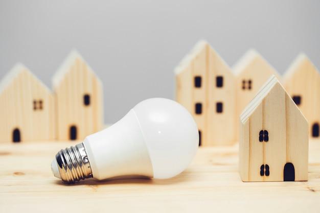 Lampadina a led con decorazione domestica in legno per illuminazione eco house a basso consumo energetico e concetto di comunità di risparmio energetico.