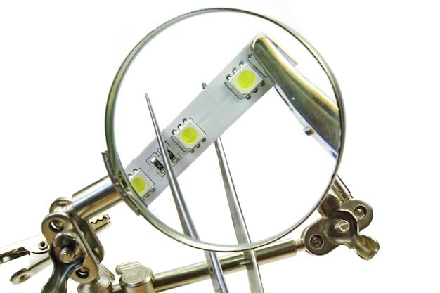 Nastro led e pinzette attraverso la lente d'ingrandimento su bianco