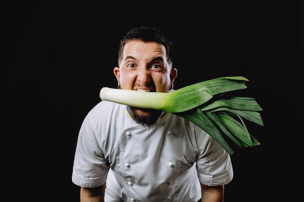 Porro in bocca allo chef. lo chef tiene un porro. uomo con i porri in bocca.