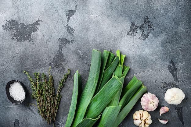 Gambi di porro con ingredienti di erbe per cucinare porri brasati, sul tavolo grigio testurizzato