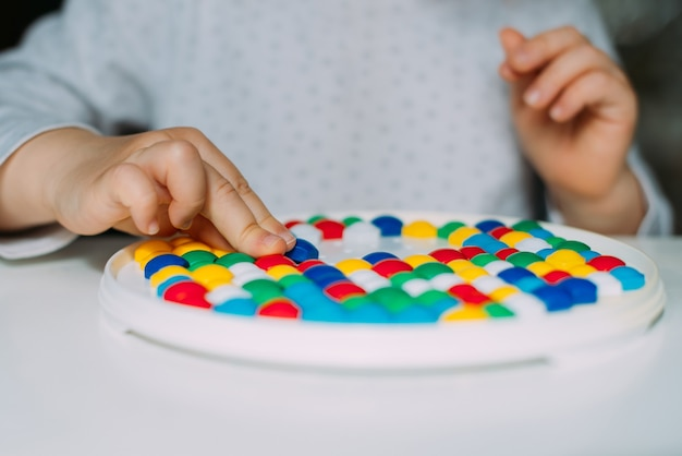 Bambino mancino che gioca a mosaico a colori da vicino.