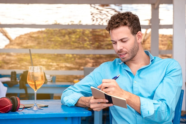 Mancino giovane seduto al bar sulla spiaggia scrivendo facendo i compiti a casa concetto di smart-working all'aperto