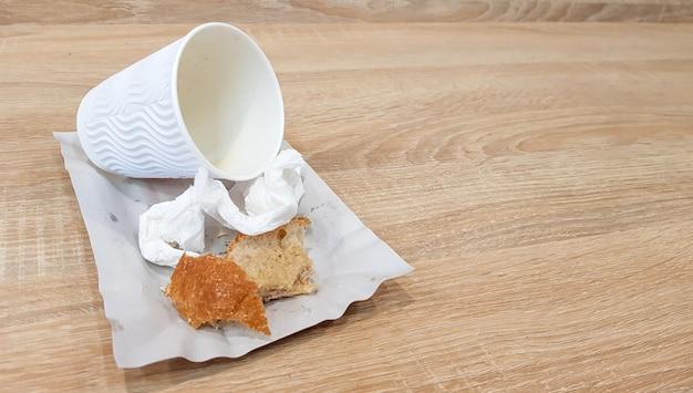 Avanzi di cibo su un piatto di carta e tazza di caffè di carta sporca vuota su un tavolo di legno in un fast food cafe.