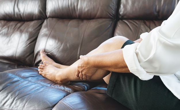 Crampi alle gambe, donna anziana che soffre di crampi alle gambe a casa, concetto di problema di salute