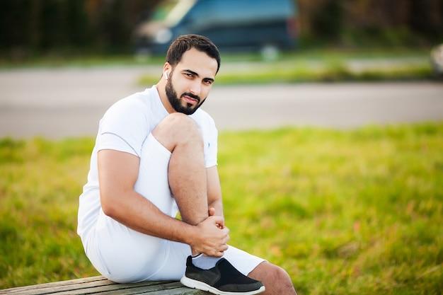 Infortunio alla gamba. atleta maschio che soffre di dolore alla gamba durante l'allenamento all'aperto.