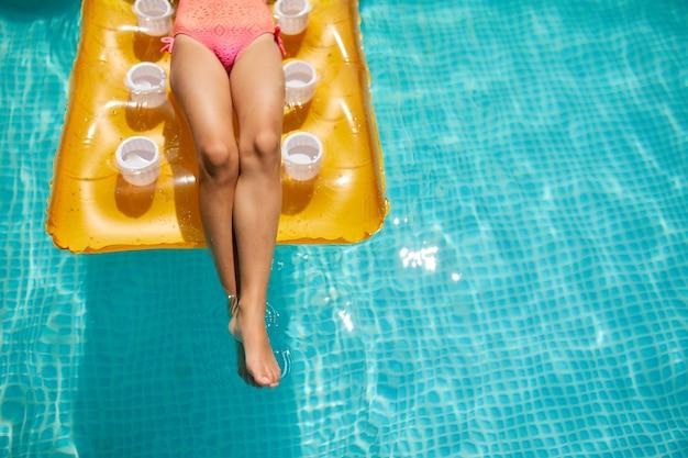 Gamba di bambina in piscina, nuota su materasso giallo gonfiabile, vacanza in famiglia, località di villeggiatura tropicale, vista dall'alto, spazio copia.
