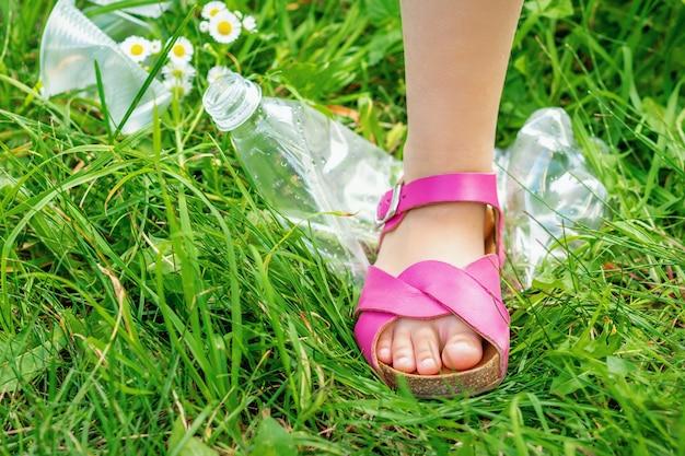 La gamba di una bambina calpesta una bottiglia di plastica sull'erba verde del parco